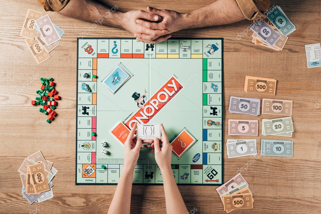 KYIV, UKRAINE - NOVEMBER 15, 2019: Cropped view of woman and man playing monopoly board game at table stock vector