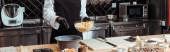 Fotografie panoramatický záběr čokoládového bonboniéra přidání bílých čokoládových lupínků do misky na kuchyňských váhách