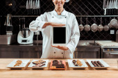 cropped view of cheerful chocolatier in holding digital tablet with blank screen near tasty chocolate candies on plates
