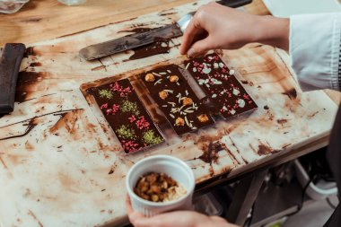 cropped view of chocolatier adding nuts in dark chocolate bar