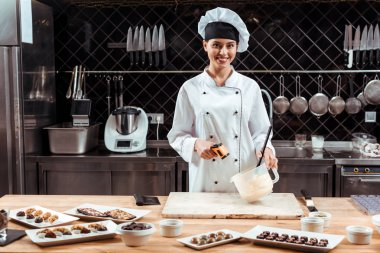 happy chocolatier in chef hat holding cooking thermometer near bowl with melted white chocolate