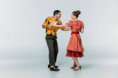 mosolygó táncosok nézik egymást, miközben táncolnak boogie-woogie szürke háttér