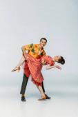 usmívající se tanečnice podporující partnera při tanci boogie-woogie na šedém pozadí