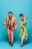 Lächelnde Tänzer blicken in die Kamera, während sie Boogie-Woogie auf blauem Hintergrund tanzen