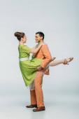 schöne Tänzerin hält Mädchen beim Tanzen Boogie-Woogie auf grauem Hintergrund
