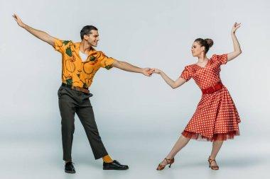 Elegant dancers holding hands while dancing boogie-woogie on grey background stock vector