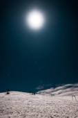 malebný pohled na lanovku v horách pokrytou sněhem proti tmavé obloze se zářícím sluncem