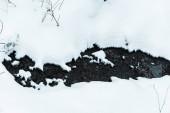 pohled shora na malý vodní potok tekoucí ve zasněžených horách