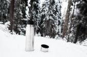 vakuová baňka s horkým nápojem na kopci pokrytém sněhem v blízkosti borového lesa