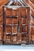 Holztür in verwittertem Rohbau mit reinem Schnee