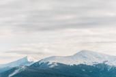malebný pohled na zasněžené hory v bílých nadýchaných mracích