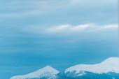 malebný pohled na zasněžené hory s bílou oblačnou oblohou