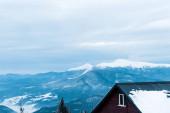 festői kilátás havas hegyek fenyőfák és faház