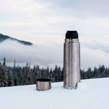 open metallic vacuum flask in snowy mountains with pine trees and white fluffy clouds