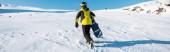 panoramatický záběr sportovce držícího snowboard při chůzi na sněhu