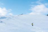 sportovec v helmě s lyžařskými hole na bílém sněhu v horách