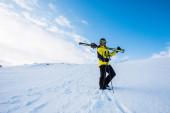 sportovec v helmě stojící s lyžařskými hole na sněhu v horách