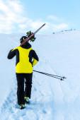 zadní pohled na lyžaře v helmě při chůzi s lyžařskými hole na sněhu