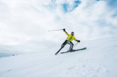 Fotografie Aufgeregter Sportler hält Skistöcke in der Hand und fährt auf weißer Piste