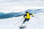 pohled zezadu na lyžaře v přilbě držící hole a lyžování na sjezdovce v zimě