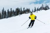 lyžař v helmě drží hole a lyžování na sjezdovce v horách