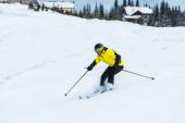 lyžař v helmě drží hole a lyžování na sjezdovce se sněhem v horách