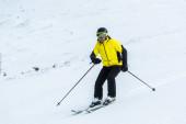 lyžař drží hole a lyžování na sjezdovce se sněhem