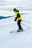 Skifahrer mit Helm hält Stöcke in der Hand und fährt draußen auf Piste
