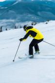 lyžař v helmě drží hole a lyžování na svahu u hor