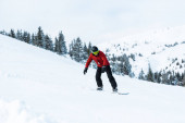athletic snowboarder in helmet riding on slope in mountains