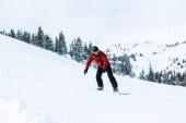 atletický snowboardista v helmě na sjezdovce v horách