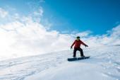 Sportlicher Snowboarder mit Helm fährt auf Piste gegen blauen Himmel mit Wolken