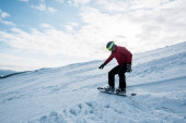 snowboarder riding on slope against blue sky with clouds in winter