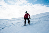 snowboardista v helmě na svahu proti modré obloze v zimě