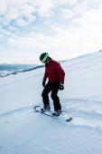 snowboardista v helmě na sjezdovce s bílým sněhem v zimě