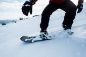 Ausgeschnittene Ansicht eines Snowboarders in Handschuhen, der im Winter am Hang mit weißem Schnee fährt