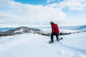 snowboardista v helmě na sjezdovce v zimním období