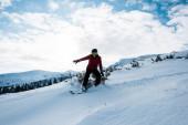 snowboardista v brýlích a helmě na svahu v zimním období