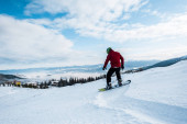 Photo snowboarder in goggles and helmet riding on slope in mountains