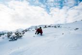 snowboardos szemüveg és sisak lovaglás lejtőn a hegyekben ellen kék ég