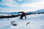 snowboarder falling while riding on slope in mountains