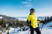 Fotografie glücklicher Skifahrer mit Skibrille, der Skistöcke gegen den blauen Himmel in den Bergen hält