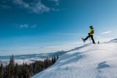 boční pohled na lyžaře držícího lyžařské hole a krok proti modré obloze v horách