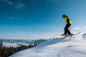 boční pohled na lyžaře držícího lyžařské hole při skákání proti modré obloze v horách