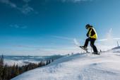 Seitenansicht eines Skifahrers, der Skistöcke hält und in den Bergen gegen den Himmel tritt