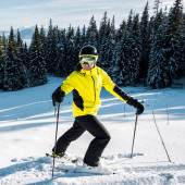 Skifahrer mit Brille und Helm auf Schnee in der Nähe von Tannen