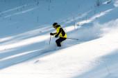 Fotografie Sportler mit Skibrille hält Skistöcke beim Skifahren im Schnee