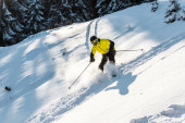 Sportler im Helm hält Skistöcke beim Skifahren auf weißem Schnee