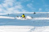 Fotografie Sportler im Helm hält Skistöcke beim Skifahren auf der Piste