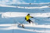 lyžař v helmě drží lyžařské hole při lyžování na sjezdovce venku